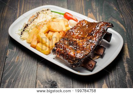 Baked pork ribs glazed in soy sauce and honey with fried potatoes close-up