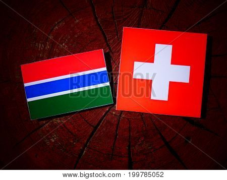 Gambian Flag With Swiss Flag On A Tree Stump Isolated