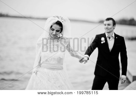Newly Married Couple Walking And Posing On The Lakeside On Their Wedding Day. Black And White Photo.