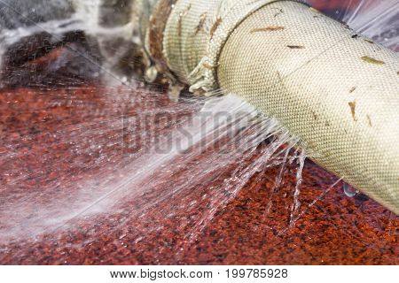 wasting water - water leaking from hole in a hose