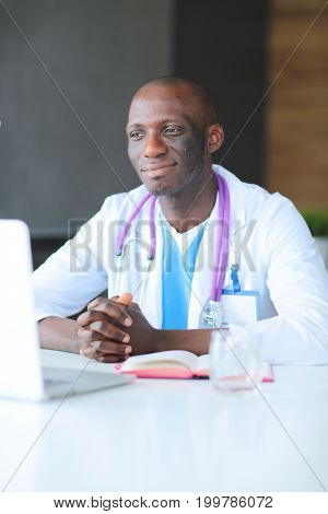 Young african doctor working on laptop at desk. Doctor. Workplace