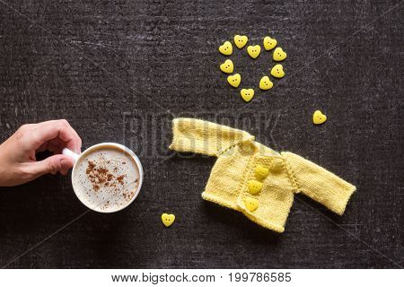 Cup of coffee, yellow knitted sweater for a doll and a heart made of buttons on a grunge black background. Female hand holding a cup.