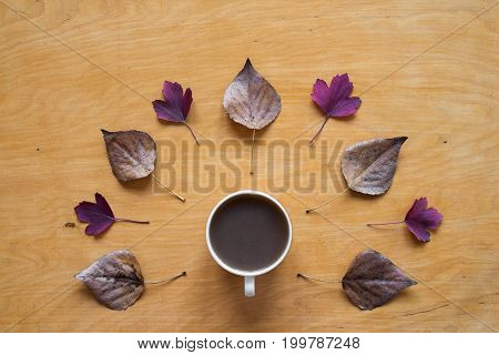 Cup of coffee and dried and red autumn leaves creatively placed on a wooden background. Shot from above.