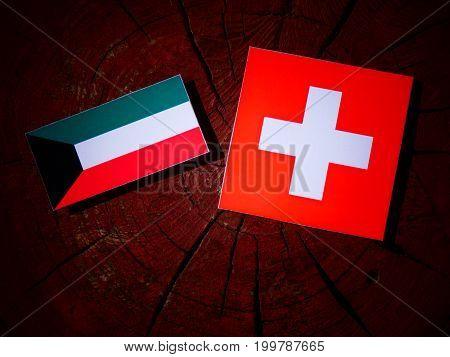 Kuwaiti Flag With Swiss Flag On A Tree Stump Isolated