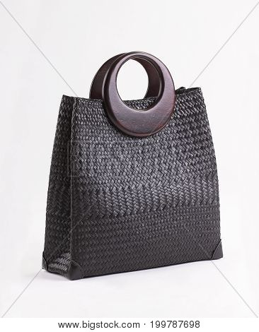 Black wicker handbag with wooden handles isolated on white background