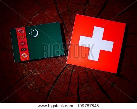 Turkmenistan Flag With Swiss Flag On A Tree Stump Isolated