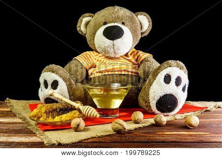 Plush bear with a vase and a spoon for honey and nuts
