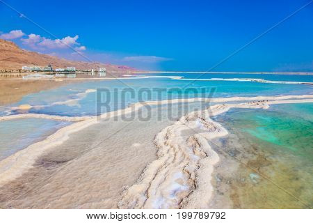 Hot summer day in Israel. Walk on the Dead Sea. The concept of medical and ecological tourism. The evaporated salt has developed into fantastic patterns