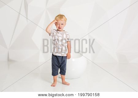 little boy in a t-shirt and shorts standing on the white floor on a white background