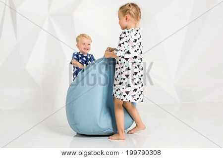 Brother and sister playing and smiling in a white studio. Little children on studio shot