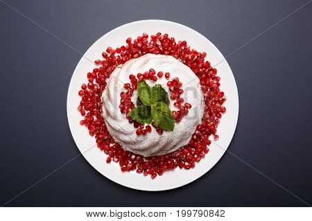 Top view of a white marble cake with sugar powder icing, red pomegranate grains and aromatic mint leaves. A plate with homemade cake on a purple background. Classic pastry recipes concept.