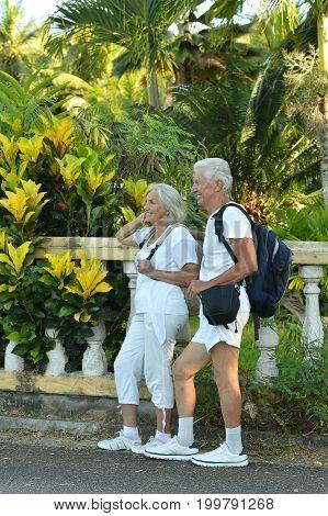 Happy senior couple with backpacks resting near railings