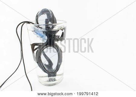 Eyeglasses for water and blue earplugs inside a glass with water. Concept. White background.