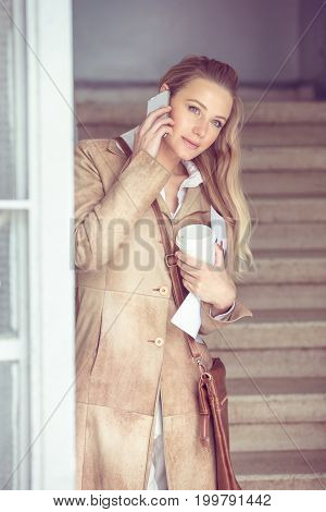 Serious business woman talking on the phone, female at work, discussing business, using modern technology of communication