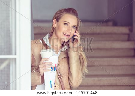 Portrait of happy smiling woman with pleasure talking on the phone, communicating with someone on coffee break, modern life of successful young people