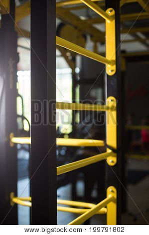 A close-up picture of a metal swedish ladder with yellow cross beams on a blurred dark gym background. Modern sports equipment. Professional fitness, gymnastics, bodybuilding training indoors.