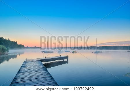 Summer afternoon landscape. Wooden pier and boat on the water at sunrise.