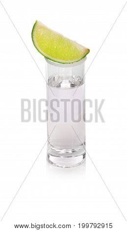 Hot Mexican tequila in a shot glass with salt and a green juicy slice of lime, beverage for cocktails that are made with tequila, including the margarita isolated on a white background.
