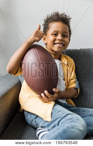 Afro Boy With American Football Ball Indoor, Sitting On Sofa