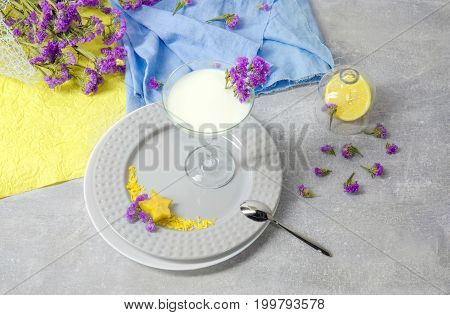 A margarita glass of fresh milky dessert on a light gray table background. Decorative purple flowers and a milkshake with a silver spoon on a plate. Vegetarian natural beverages with exotic carambola.