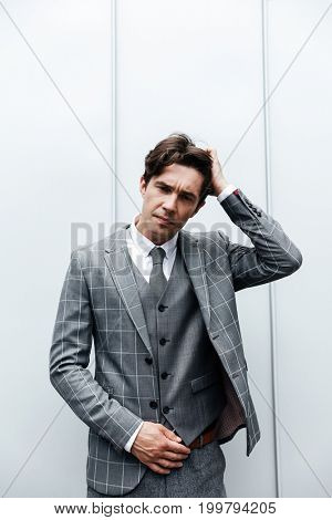Thoughtful frowning man in suit standing isolated against white wall