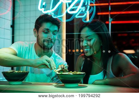 Picture of young multiethnic smiling loving couple sitting in cafe looking aside eating.
