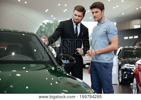 Handsome young car salesman showing a new car to the customer at the dealership