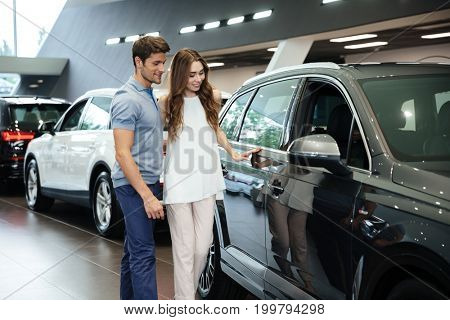 Beautiful young couple standing at the car dealership and making their decision in choosing a car