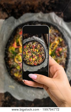 Photographing food concept - woman takes picture of italian pizza with black dough and seafood on a baking tray from the oven. Photographing on a mobile phone or tablet