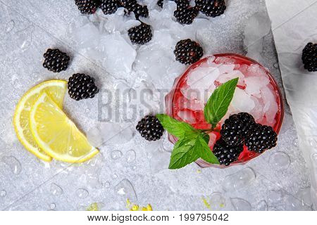 A view from above of a glass full of ice and red berry juice and fruits on a frozen white background. Close-up picture of a cold cocktail with jam, mint, lemon citron and blackberries.