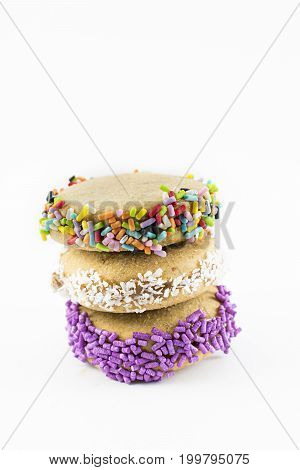 Three alfajores of cornstarch with dulce de leche or caramel. With grated coconut and colorful dragees. Tractional food. Vertical.