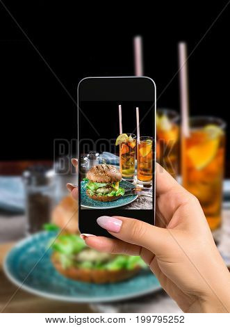Photographing food concept - woman takes picture of sandwich with chicken burger, cheese and lettuce. Burger is on the table with paper and salt and pepper shakers. As well as two cocktails log Island Iced