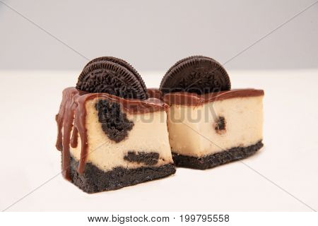 Close up of cut cheesecake with chocolate cream and cookie in it isolated over white