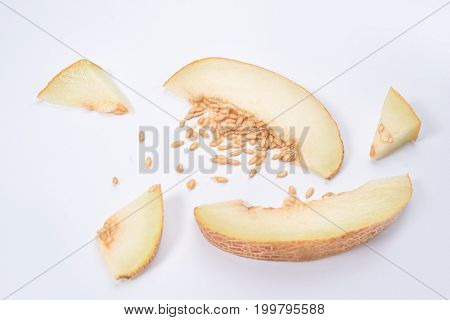 Shot of pieces of yellow melon with stones isolated over white