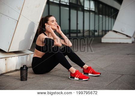 Picture of gorgeous young sports lady sitting with earphones outdoors and looking aside.