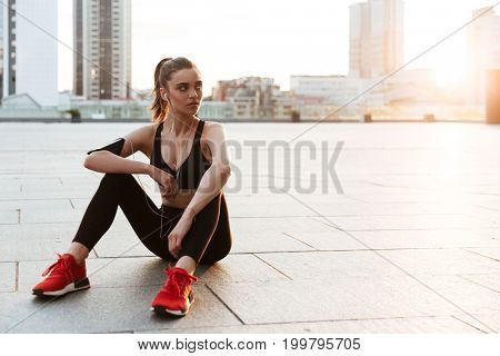 Young sportswoman resting while sitting outdoors after jogging in the morning
