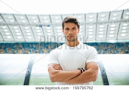 Close up of a confident male athlete standing with arms crossed at the stadium