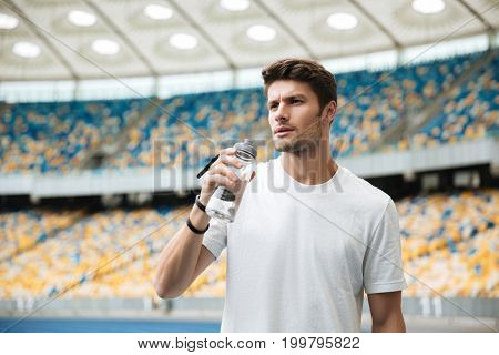 Tired sportsman holding water bottle while standing at the racetrack
