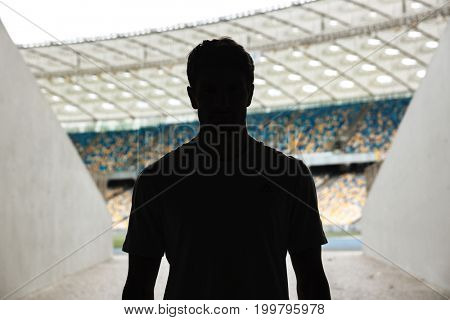 Silhouette of a man standing at the stadium entrance