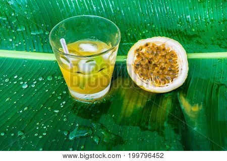 Cocktail of passion fruit served on top of a banana leaf.
