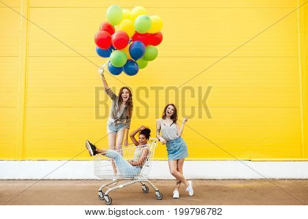 Image of young smiling women friends over yellow wall. Have fun with shopping trolley and balloons.