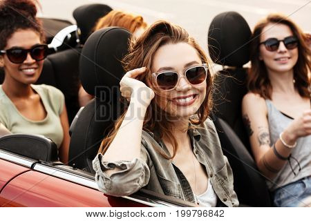 Group of cheerful young women travelling together in a car
