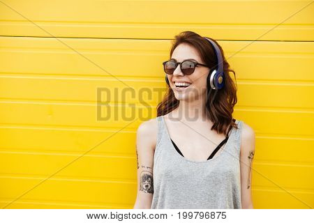 Image of happy woman standing over yellow wall listening music. Looking aside.