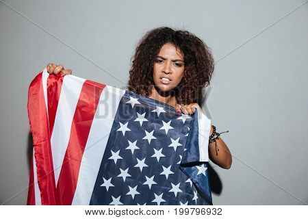 Young african woman trying to tear apart USA flag and looking at camera isolated over gray background