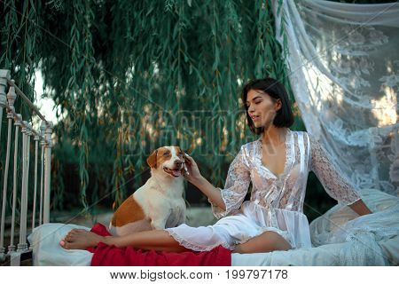 Young sexy woman in lacy peignoir sits with dog on bed with bedding and baldachin near tree. Concept of rest relaxation and serenity.