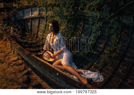 Young sexy woman in lacy peignoir with hat in her hand sits in abandoned boat at evening. She is lit by sunset.