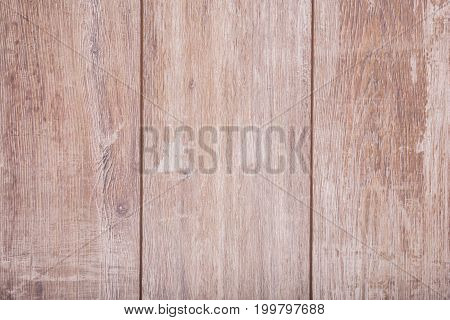 A view from above on a light brown shabby table as a background. Three old wooden planks. Rustic vintage table. Organic material. Kitchen space. Natural wooden texture.