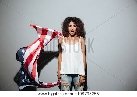 Young afro american woman holding american flag and shouting isolated over gray background
