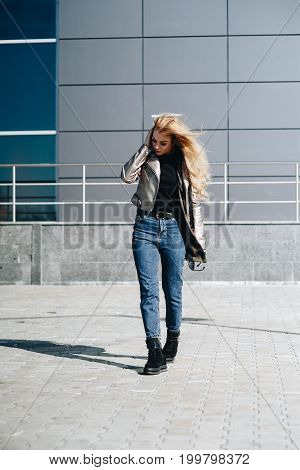 A Model In A Jacket And Jeans Poses On The Street. City Style.
