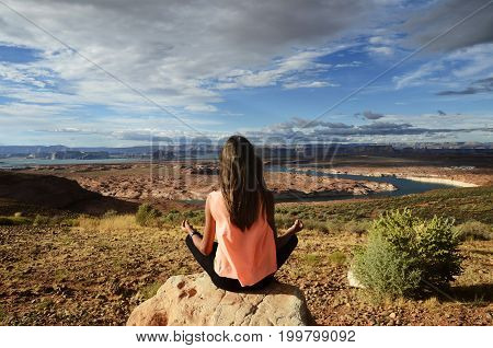 Young girl practising yoga in front of scenic view of lake powell usa